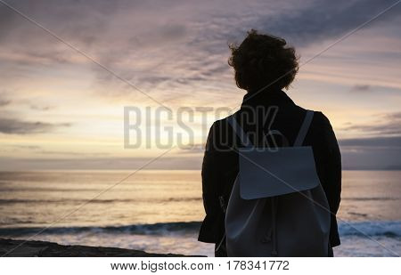 Young hipster relax on the beach on background ocean sunrise silhouette romantic person looking view evening seascape girl enjoy sunset on coast travel holidays vacation back figure on backdrop sea