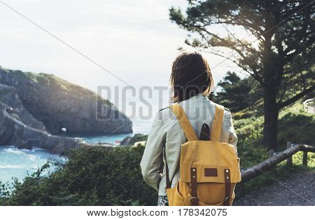 Hipster young girl with backpack enjoying sunset on seascape on peak mountain. Tourist traveler on background valley landscape view mockup. Hiker looking sunlight ocean in trip holiday in basque island