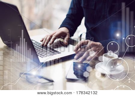Concept of digital screen, virtual connection icon, diagram, graph interfaces.Businessman working at sunny office on laptop while sitting at the wooden table.Blurred background