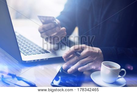 Closeup view of businessman holding credit card in hand and using smartphone, laptop computer at the wooden table.Blurred background.Horizontal.Visual effects