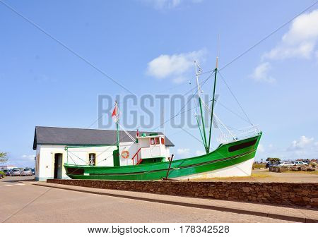 Old green fishing boat aground in France