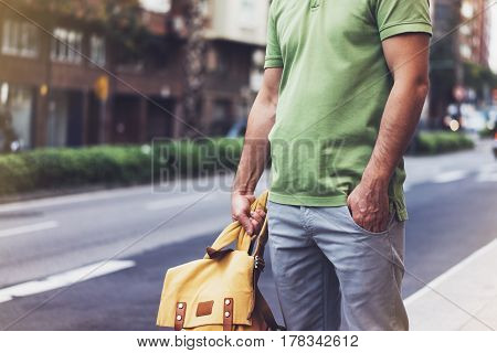 Hipster young man holding in hands backpack with map. Front view tourist traveler planning route and standing at the road on background sun summer street. Person hiker visiting the sights city mockup
