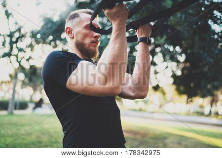 Muscular athlete exercising trx push up outside in sunny park at the morning.Attractive fittness man doing workout exercises outdoors.Blurred background.