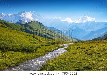 From the river shore covered with stones opens view on fantastic glacier and steep rocky mountains with green meadows which are covered with snow.Happy lifestyle. Beautiful universe.