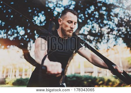 Muscular athlete exercising trx push up outside in sunny park.Fit shirtless male fitness model in crossfit exercise outdoors.Sport fitness man doing push-up workout.Blurred background.Wide horizontal