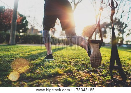 Healthy lifestyle concept.Muscular athlete exercising trx outside in sunny park.Great TRX workout.Young handsome man in sportswear doing exercising outdoors.Blurred background, flare