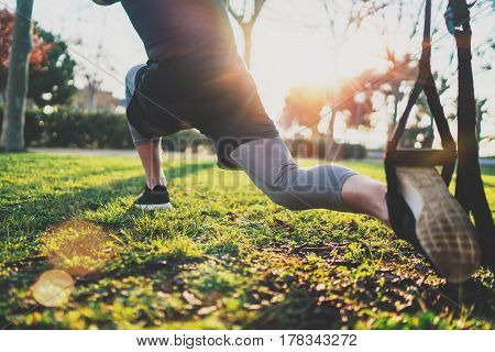 Feel your strength concept.Young athlete exercising trx outside in sunny park.Great TRX workout.Handsome man in sportswear doing exercising outdoors.Blurred background, flare