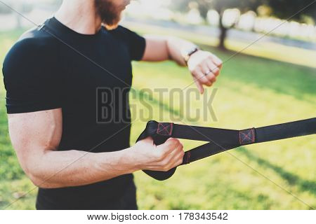 Healthy smart lifestyle concept.Muscular athlete doing great exercising TRX outside in sunny park.Young handsome man in sportswear checking sport tracker watch.Selective focus on hand.Blurred