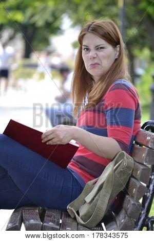 Girl make a Joke on the park bench - She does not like the bookshe is reading