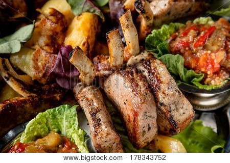 Meat plate with delicious pieces of meat salad ribs grilled vegetables potatoes and sauce. Close up image with selective focus.