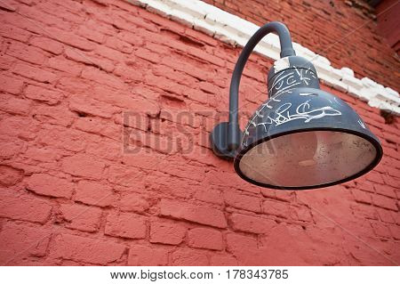 Black lantern hanging on a red wall.
