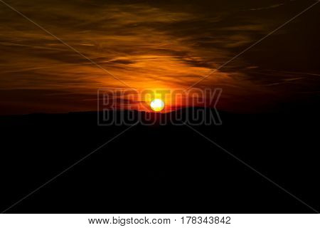 The sky is magenta and orange with alpenglow and clouds. Abstract red orange sky. Dramatic orange sky at the sunset background. The sundown behind hills. Dark in the evening.