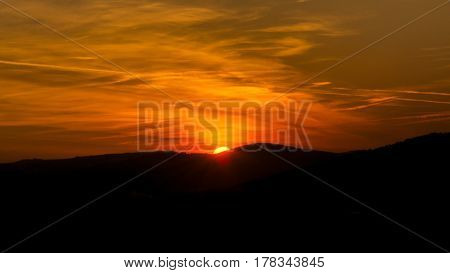 The sky is magenta and orange with alpenglow and clouds. Abstract red orange sky. Dramatic orange sky at the sunset background. The sundown behind hills.