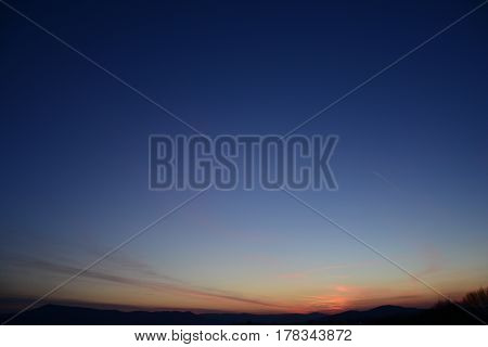 The clear sky is magenta and blue with alpenglow and few clouds. Free space for text. Abstract blue orange sky. Dramatic blue sky at the sunset background.