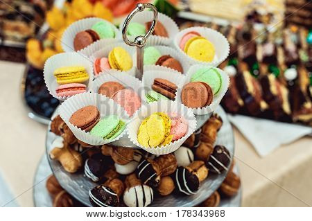 glass stand full of different sweets and macaroons. weddibg candybar