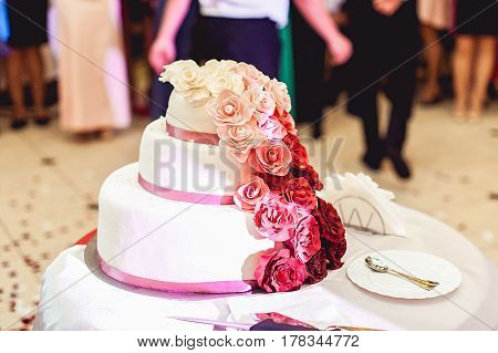 white red pink wedding cake with eatable roses on a side