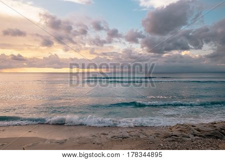 Tender sunset at a fantastic sea beach with soft pink clouds in Bali. Exotic tropical nature of Indonesia sea shore waves and orange sunset on horizon outdoor summer nature landscape