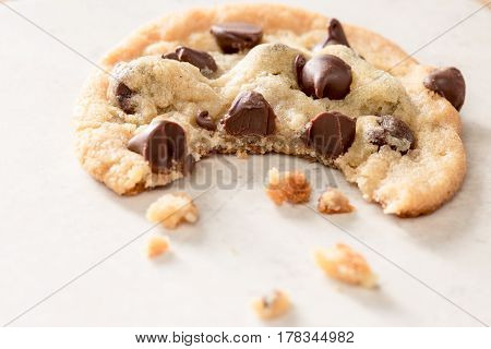 One chocolate chip cookie with a bit bite taken out