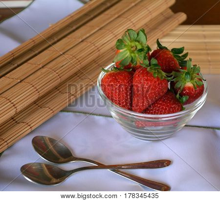 Sweet healthy dessert fresh strawberries on a glass bowl on a table.