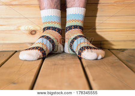 Man wearing socks with ornament. Men feet on the wooden floor.