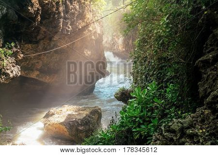 Fast tropical river with lush tropical nature and jungle forest trees and beautiful sun beam light Bali island landscape. Indonesia travel adventure with rapid torrent flows through mountains