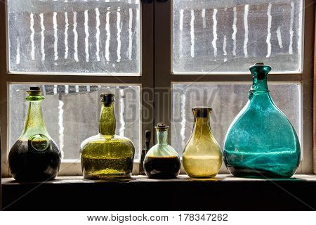 A Colorful Past; From another era in a fort along the California coast. Bottles are of different sizes and colors. Framed scratched and worn windows add character. Blue, yellow, green glass bottles.
