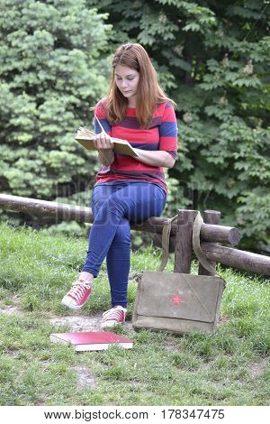 Young student in the park, reading a book in her hands