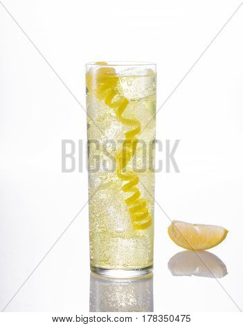 Yellow sparkling lemonade with lemon rind and slice of lemon on white reflective table