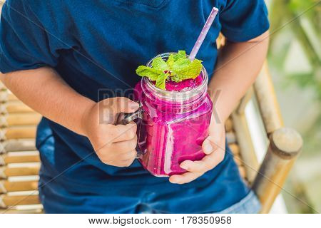 The Boy Holds Smoothies From A Dragon Fruit With A Mint Leaf And A Drinking Straw