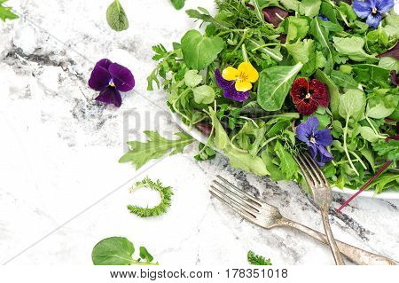 Fresh green salad with herbs and edible garden flowers. Healthy food. Detox