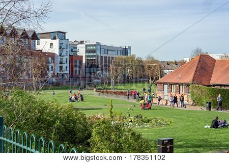 Newbury, UK. 26th March 2017. People are enjoying the sunshine on a sunny spring day in a park in central Newbury. The modern Parkway shopping precinct and apartments is in the background.