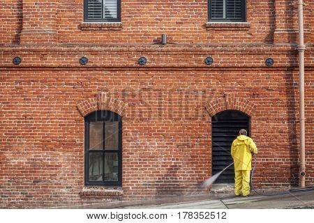 a worker in yellow rain coat washing sidewalk with a hose in front of brick house