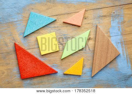 seven colorful tangram wooden pieces, a traditional Chinese puzzle game on a grunge wooden background