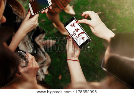 50 percentage sale concept text. woman looking on 50 percentage sale text on phone screen and pointing. stylish elegant girls at party celebration in sunny park. advertising