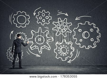 Businessman standing with back and drawing concept of teamwork and cooperation