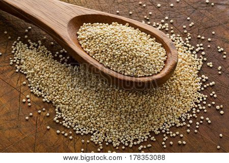 Raw whole unprocessed quinoa seed in wooden spoon on brown rustic wood board