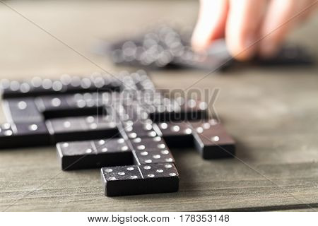 Game of domino with domino stones on wooden background with man about to make a move; selective focus on domino stone in front