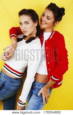lifestyle people concept: two pretty stylish modern hipster teen girl having fun together, happy smiling making selfie close up on yellow background, diverse type of girls