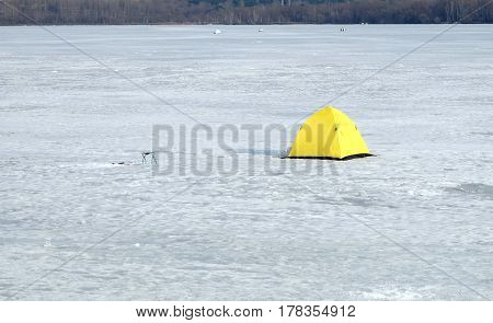 Landscape with fisherman tents in snow on frozen river in winter day against forest at far closeup