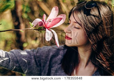 Stylish Beautiful Hipster Woman Smelling Magnolia Flower In Sunny Green Park. Tender Beauty Of Bloom