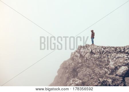Man trekking in mountains alone. Cold weather, fog and clouds. Winter hiking.