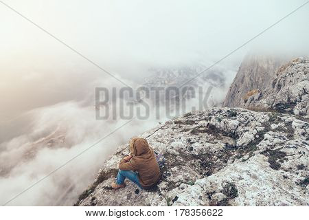 Human trekking in mountains alone. Cold weather, fog and clouds. Winter hiking.
