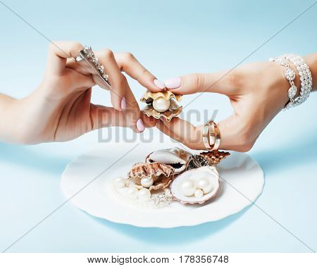 beautiful woman hands with pink manicure holding plate with pearls and sea shells, luxury jewelry concept close up