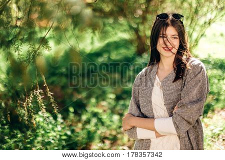 Stylish Beautiful Hipster Woman Relaxing Under Green Branches In Sunny Park. Young Girl With Sunglas