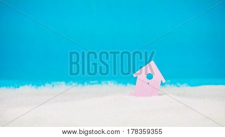 Symbol of little lilac house on the sand with bright blue background.