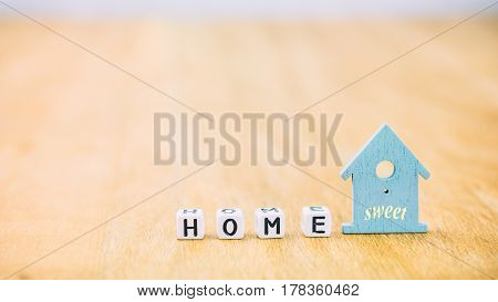 HOME Sweet horizontal word of cube letters behind blue house symbol on wooden surface.