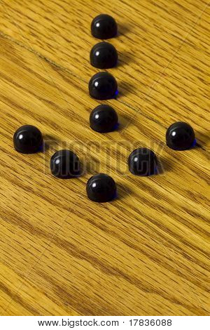 Blue marbles on a game board forming an arrow. poster