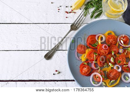 Salad with tomatoes pepper and red onion with sauce on a gray plate on a white background.