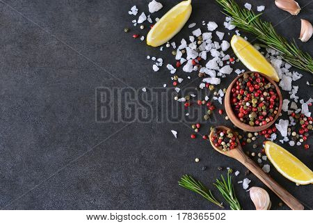 Mix of peppers with salt rosemary and garlic on shale stone. Black food background with spices. Top view.