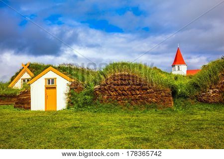 Museum-estate Glaumbaer, Iceland. The concept of the historical and cultural tourism. Church bell tower with a peaked red roof in old village of  houses covered with turf